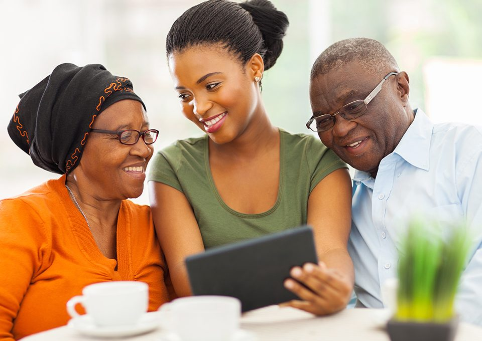 african family at home using tablet pc