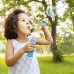 Beautiful little girl blowing bubbles in park. Horizontal Shot.