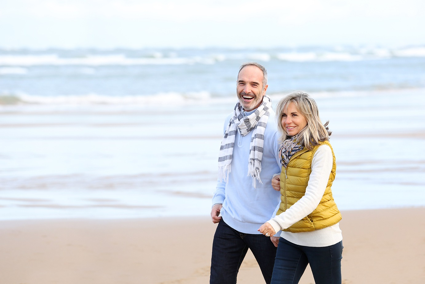 Happy middle aged couple walking on beach on a winter day. Covenant Care.