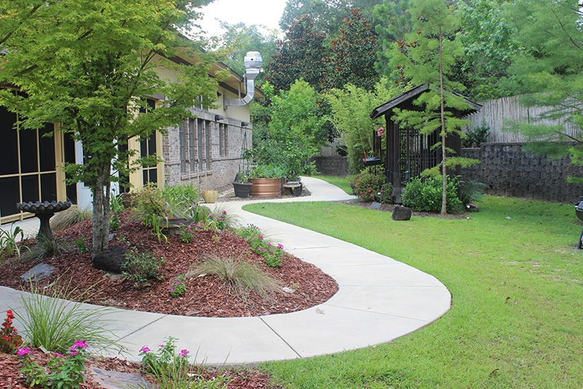 Pretty green backyard with flowers The Residence Covenant Care