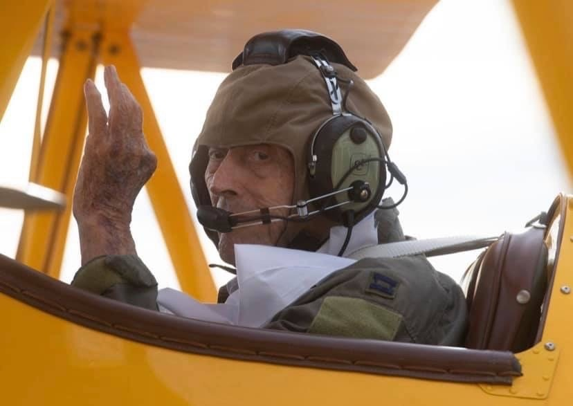 Capt Albert Lane with headset seated in a Biplane. Covenant Care