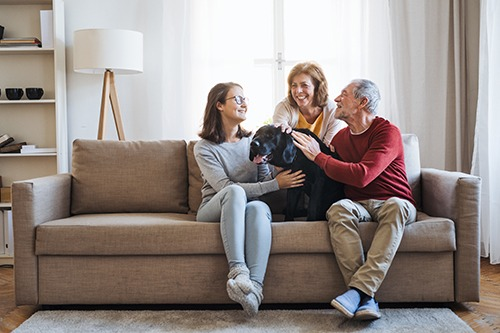 A senior couple with a teenage girl sitting on a sofa with pet dog. Covenant Care