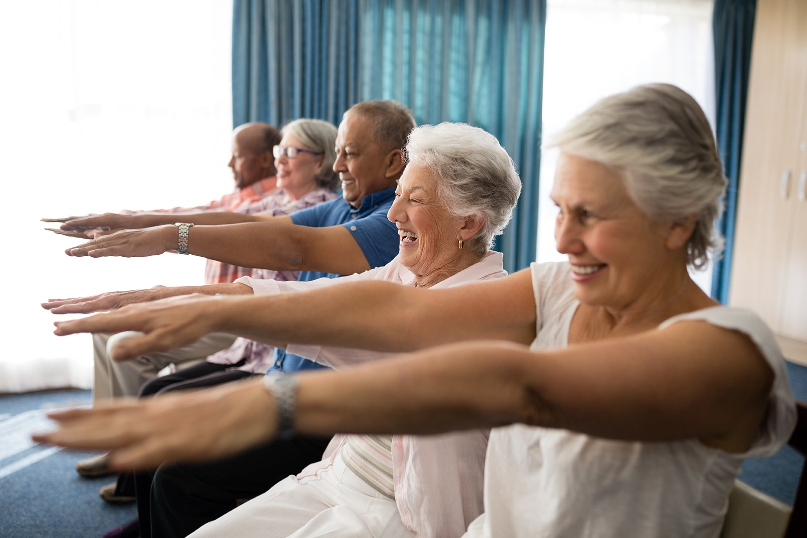 Cheerful senior people exercising with arms raised. Covenant Care