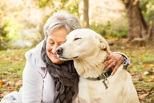 Senior woman smiling and hugging dog with eyes closed. Covenant Care