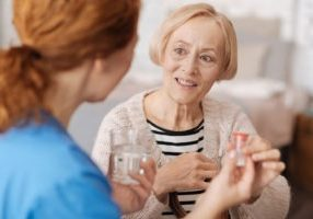 Happy Senior receiving medication from a health care worker. Covenant Care